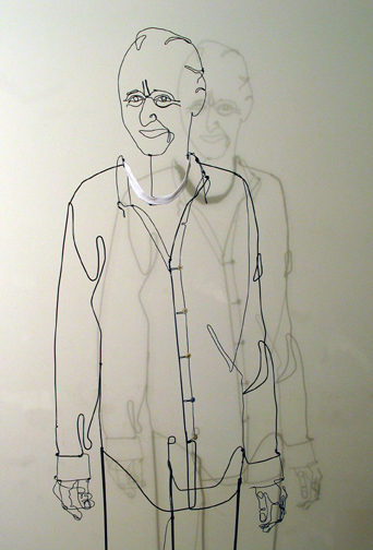 Figurative wire sculpture of standing man with white collar